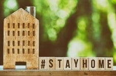 A small wooden house stands next to a number of wooden blocks spelling out #StayHome.