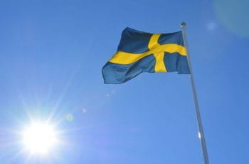 The Swedish national flag soaring high in the sky on a clear blue sunny day.