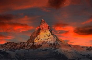 The famous Swiss Matterhorn mountain surrounded by red skies.