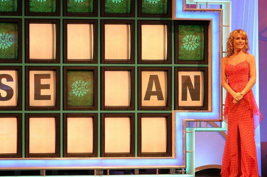 Vanna White stands next to the famous letter puzzle on the TV show Wheel of Fortune.
