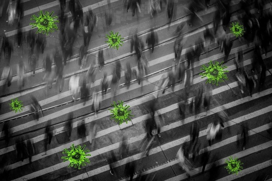 A crowd moves through a busy street superimposed with images of bright green coronavirus particles.