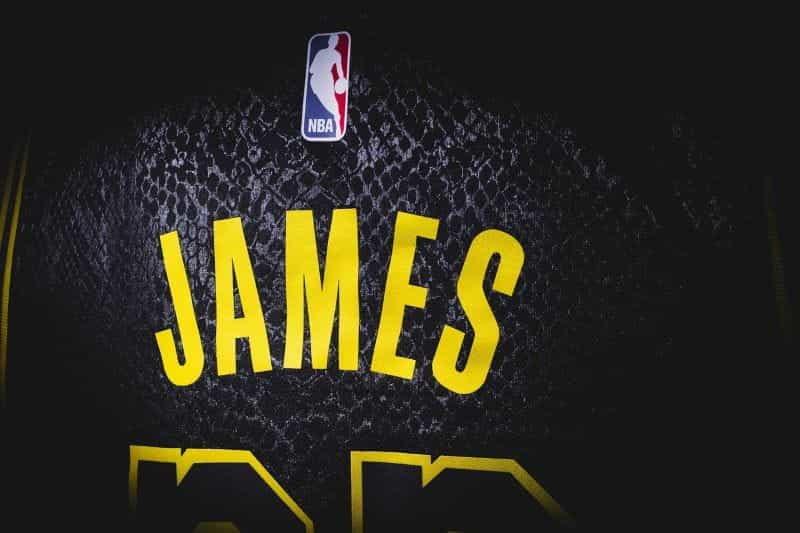 Seragam basket hitam bertuliskan JAMES dengan huruf kuning.