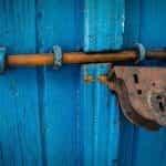 Pintu kayu biru tertutup rapat berkat baut dan gembok.
