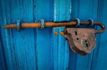 A blue wooden door secured shut thanks to a bolt and padlock.