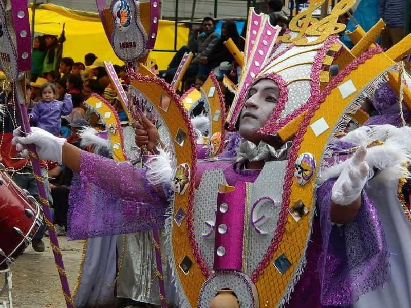 Seorang penari pria yang mengenakan kostum warna-warni selama Karnaval di Cajamarca, Peru.