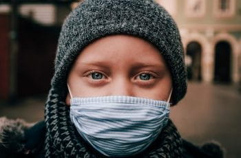 A child wearing a nose and mask covering during the coronavirus pandemic, staring into the camera.