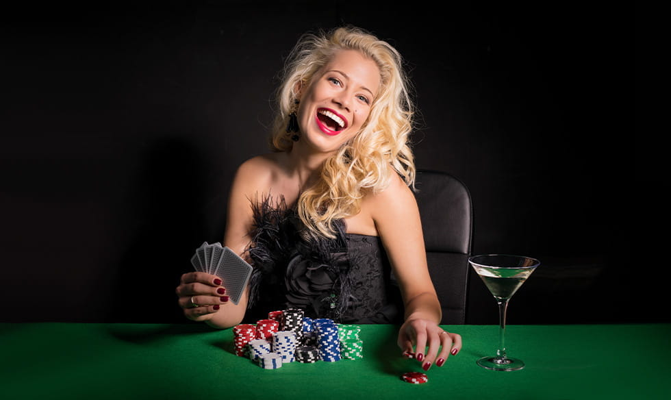 A woman sitting at a gambling table, with playing cards and casino chips.