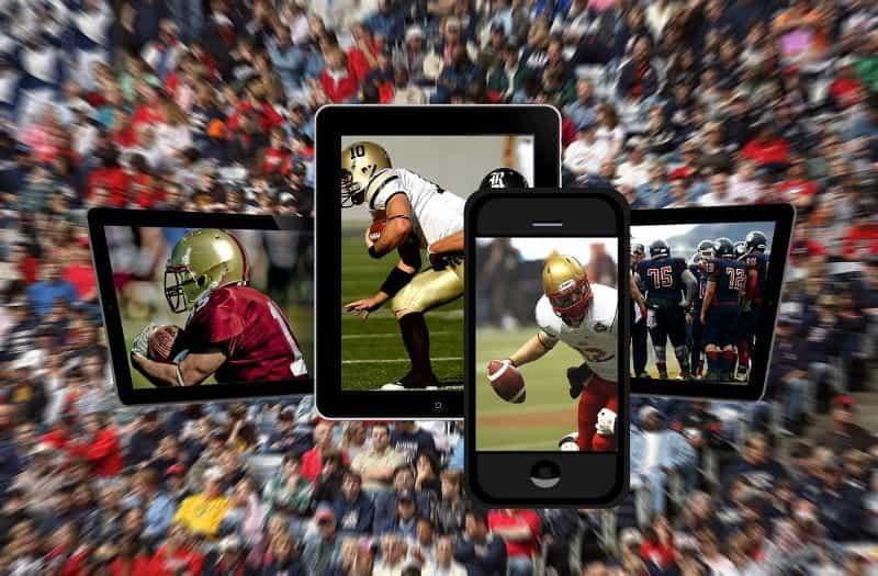 Tiga tablet digital dan sebuah ponsel pintar memainkan permainan sepak bola dengan latar belakang kabur para penggemar olahraga di sebuah stadion.
