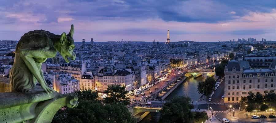Gargoyle yang menghadap ke ibu kota Prancis, Paris pada malam hari, dengan Menara Eiffel yang ikonik terlihat di kejauhan.
