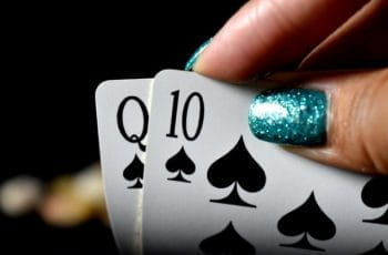 A hand with glittery nails holds some playing cards.