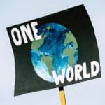 An environmental placard with planet earth painted on it and one world.