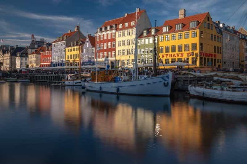 Distrik Nyhavn di ibu kota Denmark, Kopenhagen, dengan jalur pejalan kaki dan kapal yang berlabuh terlihat jelas.