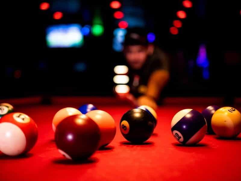 Seorang pria bermain biliar di bar olahraga.