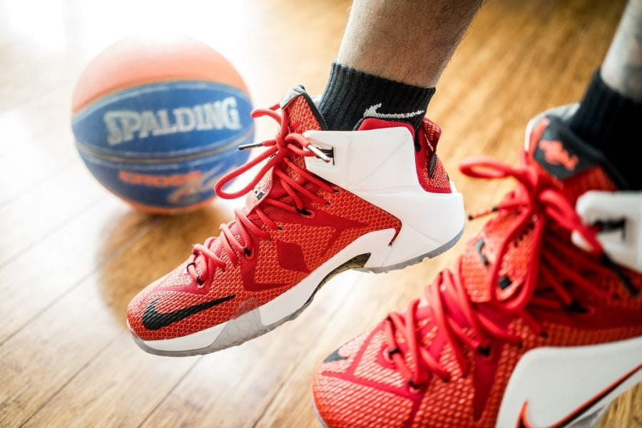 Kaki yang mengenakan sepatu kets basket Nike merah menjuntai di atas lapangan basket, tempat bola basket berada di latar belakang.