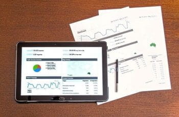 The results of a report, featuring graphs and charts displayed across both a computer tablet, as well as printed out finalized documents.