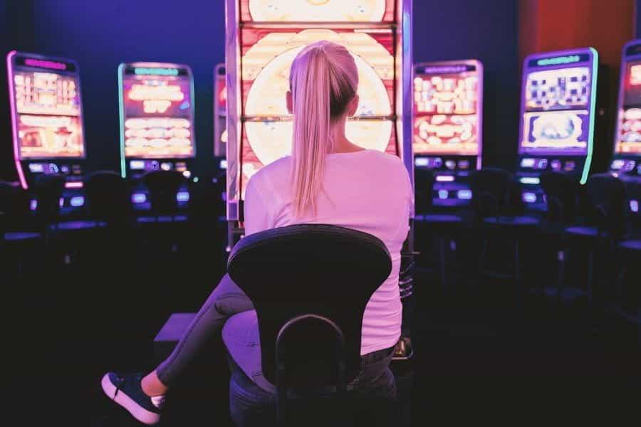 Seorang wanita yang duduk di depan pilihan mesin slot di kasino, mungkin sedang merencanakan langkah selanjutnya.