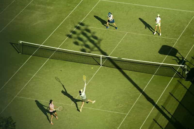 Pertandingan tenis duet wanita di lapangan rumput, dengan matahari yang membuat bayangan dramatis melintasi lapangan.