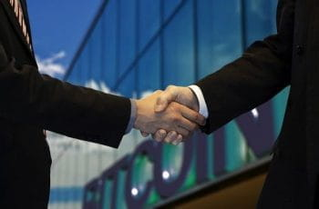 Two people shaking hands as they secure a new deal in front of a building with a large Bitcoin sign on its front.