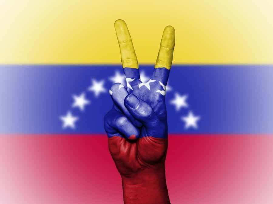 Sebuah tangan membuat tanda perdamaian di depan bendera Venezuela.