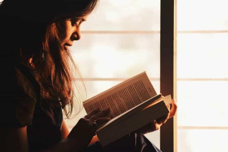 Seorang wanita duduk membaca buku.