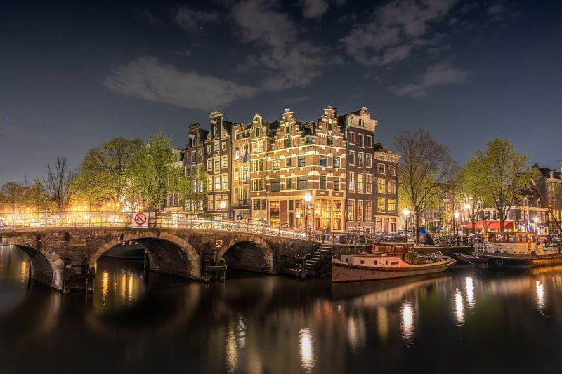 Nightfall in the Dutch capital of Amsterdam, with one of the city's countless iconic bridges in plain view.