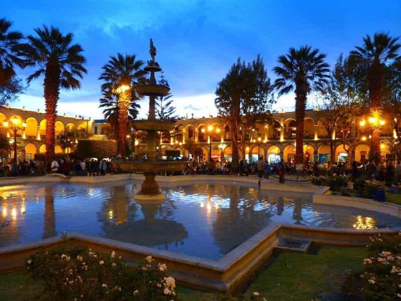 Senja di plaza luar ruangan yang ramai dengan air mancur besar di Arequipa, Peru.