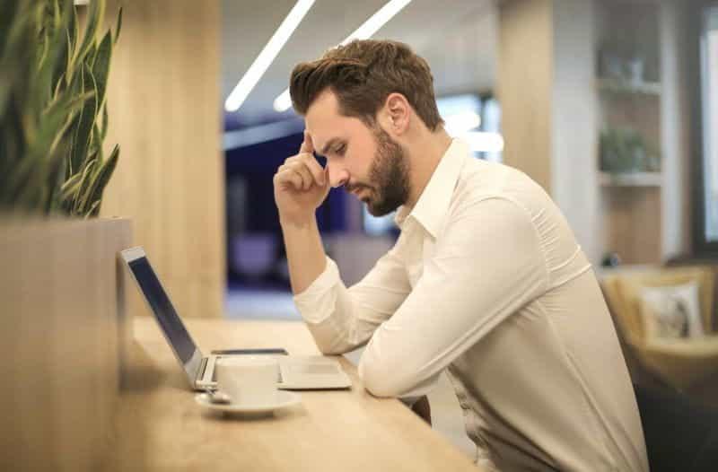 Seorang pria dengan secangkir kopi menggunakan laptop.