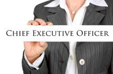 A businesswoman in a suit holds a sign that says chief executive officer.