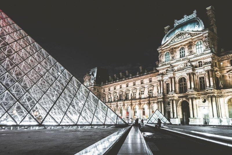 The Louvre museum in the French capital city of Paris illuminated at night.