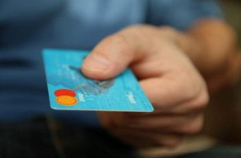 A hand holding out a blue debit card.