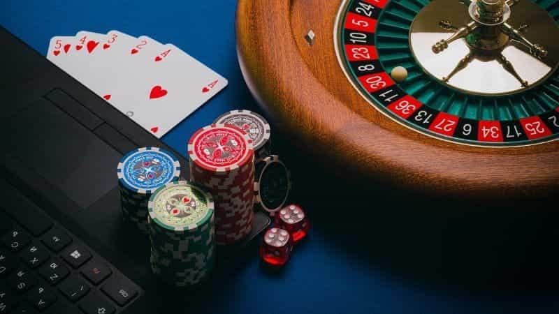 Roda roulette, kartu, chip poker, dan dadu di sebelah laptop.