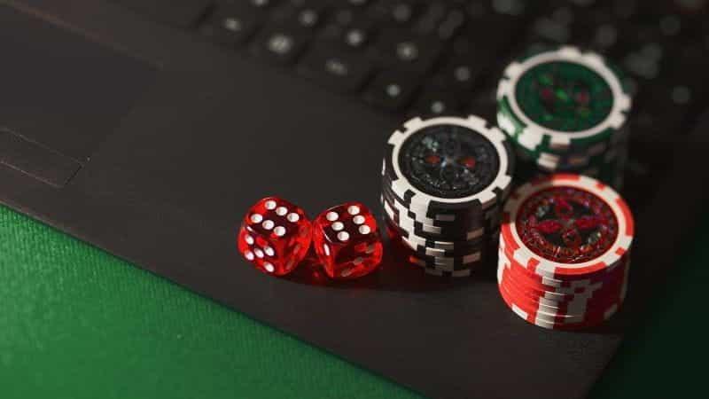 Chip dadu dan poker di laptop, dengan nuansa hijau.