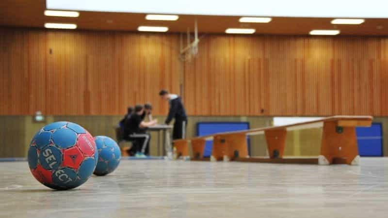 Sepasang bola tangan yang duduk berdampingan di dalam gym dalam ruangan atau fasilitas lapangan bola tangan.