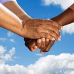 Three hands joining together against a blue sky with white clouds backdrop.