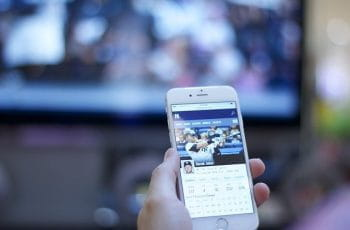 A person holds an iPhone 6 with a mobile sports app open to the stats of Derek Jeter while a baseball game plays on a TV in front of them.