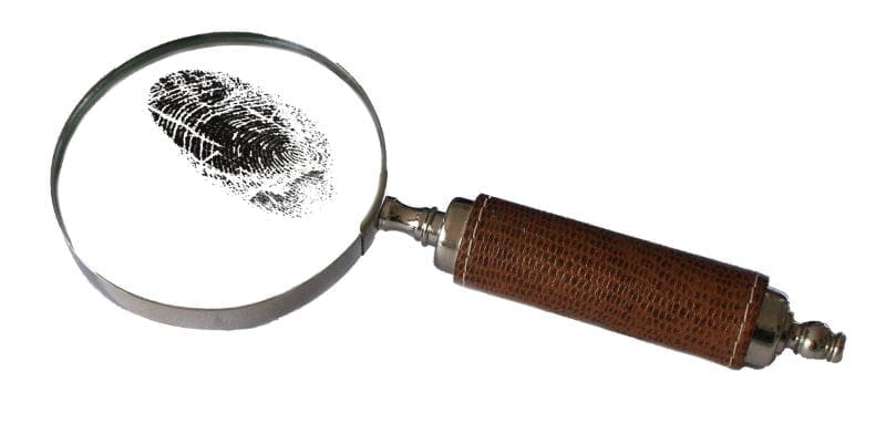 A magnifying glass takes a close look at a fingerprint.