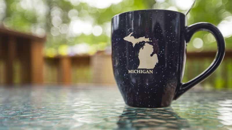 Mug bertuliskan Michigan di bawah gambar negara bagian berada di atas meja.