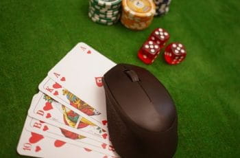 A set of cards resting underneath a computer mouse, which sits alongside three die and several stacks of poker chips.
