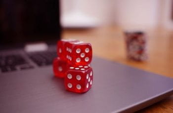 Red dice stacked on a laptop.