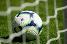 A Premier League football in a goal net.