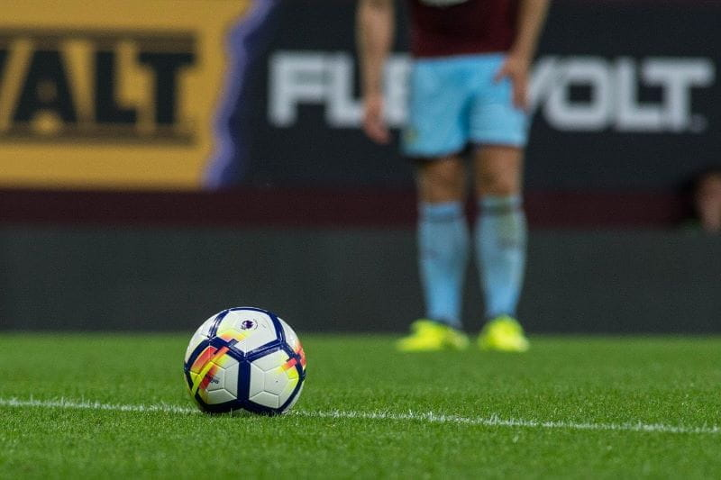 Seorang pesepakbola berdiri di belakang bola di lapangan.