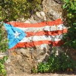 The Puerto Rico flag drawn with chalk on a rock wall.