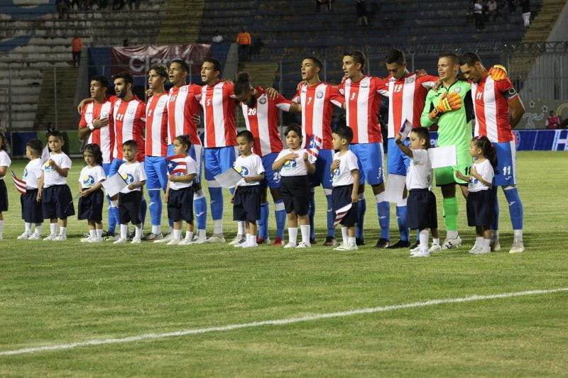 Puerto Rico's national soccer team stands with their arms around each other singing a national anthem.