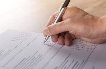 A person filling out a survey or report by checking boxes using a pen in their hand.