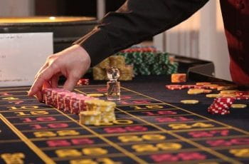 A dealer lines up stacks of chips on a roulette table in a casino.
