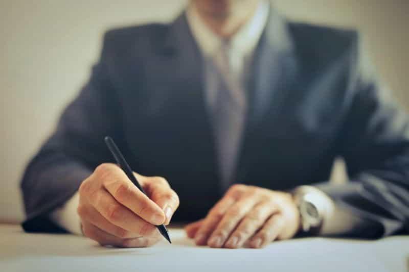 Seorang pengusaha berjas menandatangani kesepakatan.