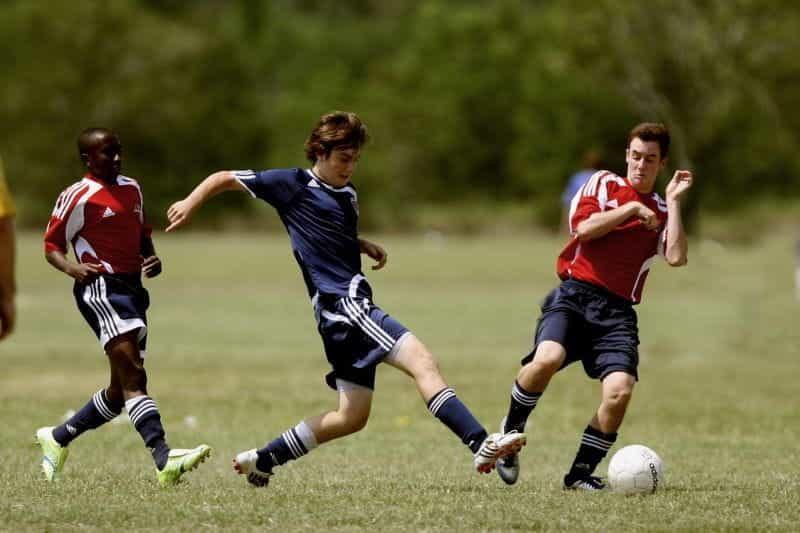 Tiga pemain sepak bola bermain di lapangan.