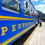 A blue Perurail train at an outdoor train station on a sunny day.