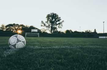 A football and a goal on an empty football field.