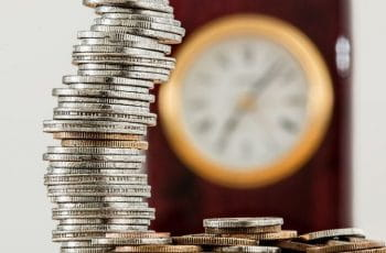 A stack of coins, with a clock in the background.